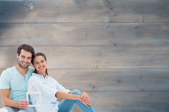 Composite image of cute couple sitting holding a house shape Stock Image