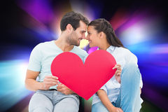 Composite image of cute couple sitting holding red heart Stock Image