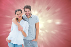 Composite image of cute couple smiling at camera. Cute couple smiling at camera against valentines heart design Stock Photo