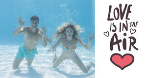 Composite image of cute couple smiling at camera underwater in the swimming pool Stock Images