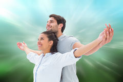 Composite image of cute couple standing with arms out Royalty Free Stock Image