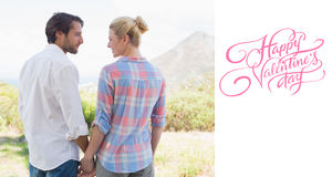 Composite image of cute couple standing hand in hand smiling at each other Stock Photography