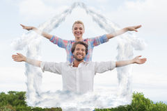 Composite image of cute couple standing outside with arms outstretched Royalty Free Stock Image
