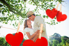 Composite image of cute couple standing in the park embracing Royalty Free Stock Images