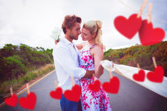 Composite image of cute couple standing on the road hugging Stock Images
