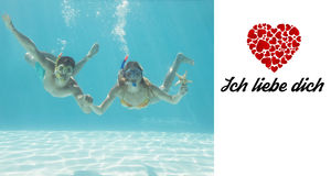 Composite image of cute couple underwater in the swimming pool with snorkel and starfish Stock Photo