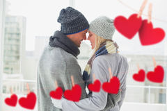 Composite image of cute couple in warm clothing hugging Stock Photography