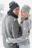 Composite image of cute couple in warm clothing hugging smiling at camera Royalty Free Stock Photo