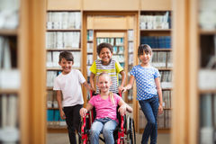 Composite image of cute disabled pupil smiling at camera with her friends. Cute disabled pupil smiling at camera with her friends against library Royalty Free Stock Images