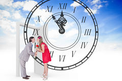 Composite image of cute geeky couple kissing Royalty Free Stock Photography