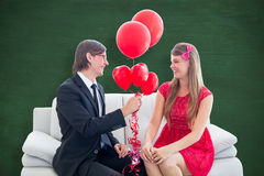 A Composite image of cute geeky couple with red balloons. Cute geeky couple with red balloons  against green chalkboard Royalty Free Stock Photography