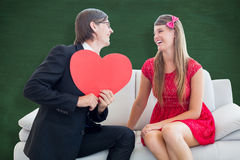 A Composite image of cute geeky couple with red heart shape Stock Image