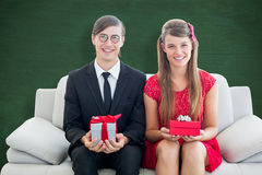 A Composite image of cute geeky couple smiling and holding gift Royalty Free Stock Image