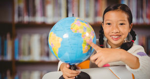 Composite image of cute girl pointing on a globe Stock Images