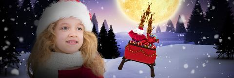 Composite image of cute girl in santa hat. Cute girl in santa hat against christmas house under full moon royalty free stock image