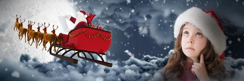 Composite image of cute girl in santa hat. Cute girl in santa hat against moon shining between clouds royalty free stock photography