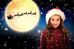 Composite image of cute girl in santa hat. Cute girl in santa hat against white background with vignette royalty free stock image