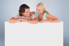 Composite image of cute happy couple leaning on a whiteboard Stock Photos