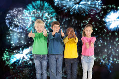 Composite image of cute kids showing thumbs up royalty free stock photo