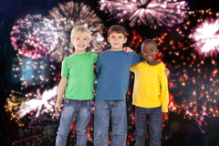 Composite image of cute kids smiling. Cute kids smiling against colourful fireworks exploding on black background Royalty Free Stock Photography