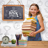 Composite image of cute little girl carrying books in library royalty free stock image