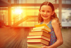 Composite image of cute little girl carrying books in library Royalty Free Stock Images