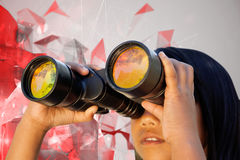 Composite image of cute little girl looking through binoculars. Cute little girl looking through binoculars against angular design royalty free stock photo