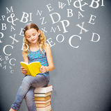 Composite image of cute little girl reading book in library Royalty Free Stock Images