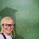 Composite image of cute pupil with graduate shadow. In classroom Royalty Free Stock Image