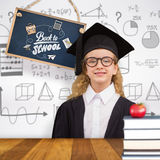 Composite image of cute pupil in graduation robe Stock Photo