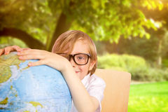 Composite image of cute pupil holding globe Stock Image