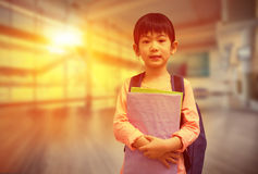 Composite image of cute pupil looking at camera holding notepad Royalty Free Stock Photography