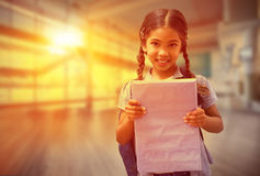 Composite image of cute pupil smiling at camera holding notepad Stock Photography