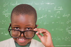 Composite image of cute pupil tilting glasses. Cute pupil tilting glasses against rocket science theory Stock Photo