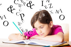 Composite image of cute pupil working at her desk Royalty Free Stock Photo