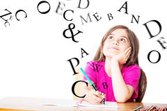Composite image of cute pupil working at her desk Royalty Free Stock Photography