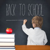 Composite image of cute pupil writing on board Royalty Free Stock Images