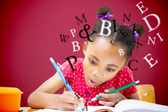 Composite image of cute pupil writing at desk in classroom Royalty Free Stock Image