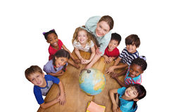 Composite image of cute pupils smiling around a globe in classroom with teacher Royalty Free Stock Photos