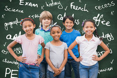 Composite image of cute pupils smiling at camera in classroom Royalty Free Stock Image