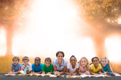 Composite image of cute pupils smiling at camera with teacher Royalty Free Stock Image