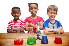 Composite image of cute pupils standing with arms crossed behind beaker Royalty Free Stock Photography