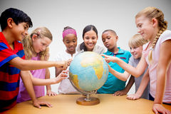 Composite image of cute pupils and teacher looking at globe in library Stock Photo