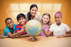 Composite image of cute pupils and teacher looking at globe in library Stock Images