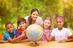 Composite image of cute pupils and teacher looking at globe in library Royalty Free Stock Photography