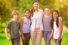 Composite image of cute pupils and teacher smiling at camera in computer class Royalty Free Stock Image