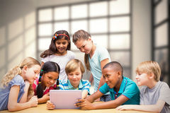 Composite image of cute pupils using tablet computer in library Royalty Free Stock Photos