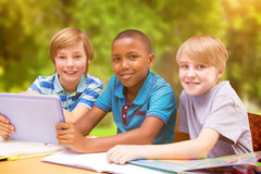 Composite image of cute pupils using tablet computer in library Royalty Free Stock Photography