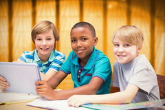 Composite image of cute pupils using tablet computer in library Royalty Free Stock Photo