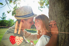 Composite image of cute smiling couple leaning against tree in the park Royalty Free Stock Photo